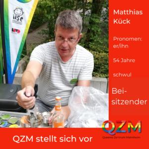 Matthias bedient die Buttonmaschine an einem sonnigen Tag draußen. Zusätzliche Infos: Pronomen: er/ihn, 54 Jahre, schwul, Beistizender