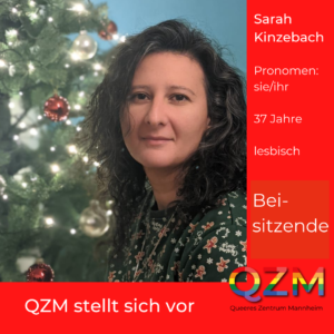 Sarah vor einem Weihnachtsbaum, roter Hintergrund. Zusätzliche Info: Pronomen sie/ihr, 37 Jahre, lesbisch, Beisitzende