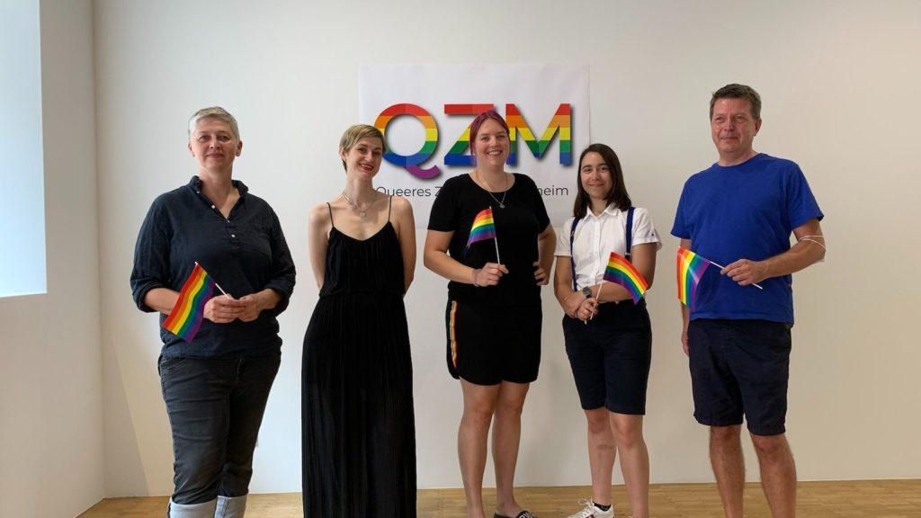 die fünf Vorstandmitglieder schwenken Regenbogenfähnchen und stehen vor einem QZM-Logo in Regenbogenfarben. Von links nach rechts: Susanne Hun, Kristina Scheuermann, Johannah Illgner, Cilly Dickmann und Matthias Kück
